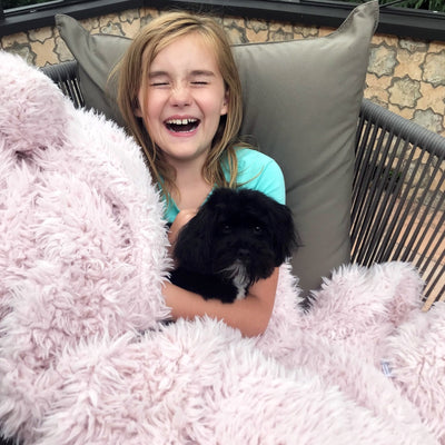 Young girl laughing holding a black dog, Little Guardian Angle Blanket in Dusty Pink, child size blanket, llama fabric