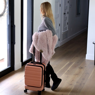 Woman with a suitcase traveling with Little Guardian Angel Blanket in Dusty Pink
