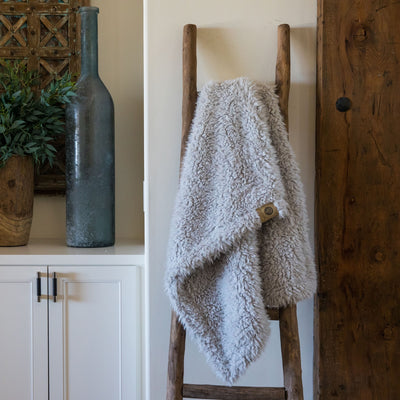 Little Guardian Angel blanket in Silver Cloud, llama fabric, on wooden ladder in front of white cabinets