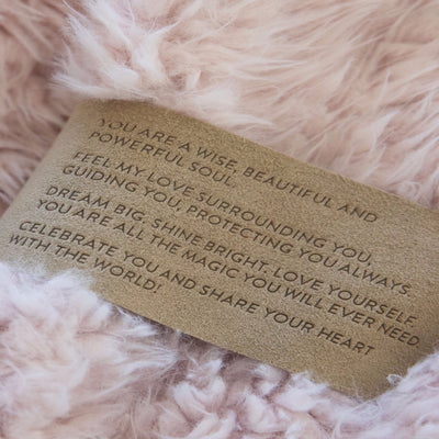Close up of a Love Snap label with text, on a Dusty Pink Guardian Angel Blanket
