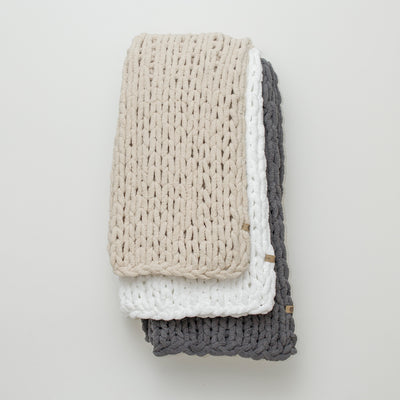 Staked chunky knit blankets from the Big Infinite Love Collection in: Oat, White, and Slate