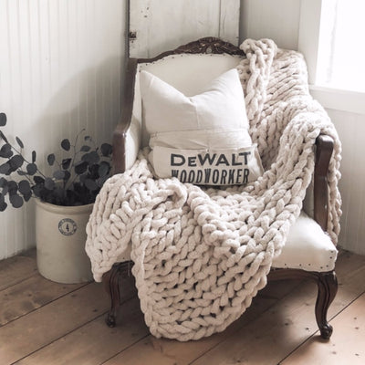 Big Infinite Love Blanket in Oat, draped over a vintage chair, decorative pillows, wooden floors
