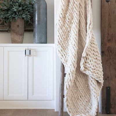 Big Infinite Love Blanket in Oat, chenille chunky knit, on a wooden ladder in front of white cabinets