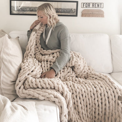 Woman lounging on white sofa, cuddled in her Big Infinite Love Blanket in Oat, chunky knit blanket