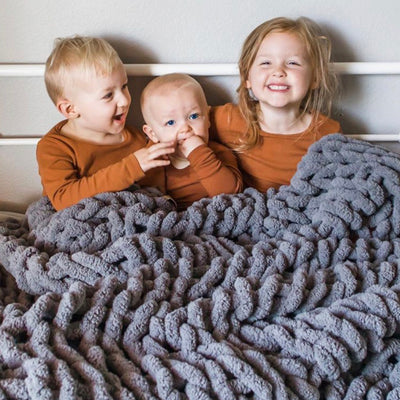 Three toddlers cuddling and giggling, under their Big Infinite Love Blanket in Slate, chunky knit blanket, family blanket