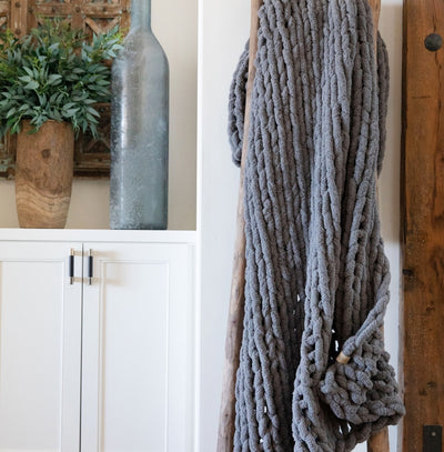 Big Infinite Love Blanket in Slate, chenille chunky knit, on a wooden ladder in front of white cabinets
