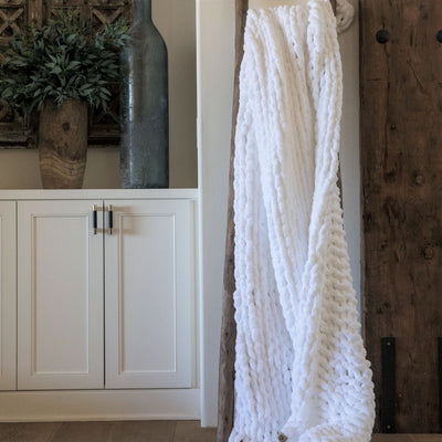 Big Infinite Love Blanket in Whisper White, chenille chunky knit, on a wooden ladder in front of white cabinets