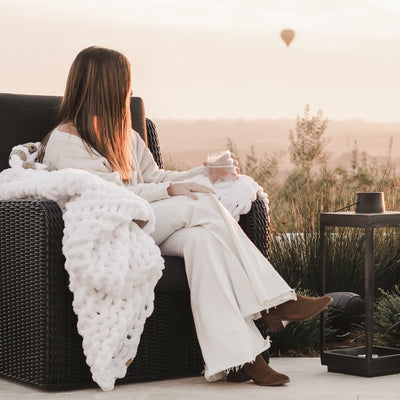 Young woman sitting on a chair outside, cozied up in the Whisper White Infinite Love Blanket, hot air balloons in the distance