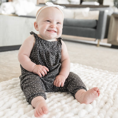 Baby girl smiling sitting on a Little Infinite Love Blanket in White, chunky knit nursery blanket