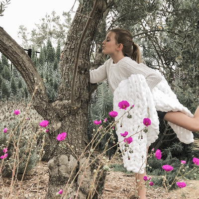 Young girl posing with a tree holding her Little Infinite Love Blanket in White, purple flowers around Gia Poling BIG LOViE