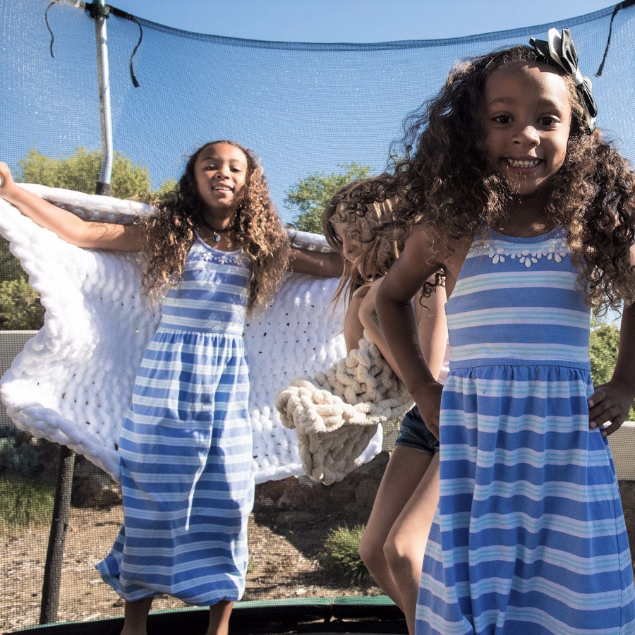 Three young girls in blue and white dresses, jumping on trampoline playing with their Little Infinite Love Blanket in White and Oat