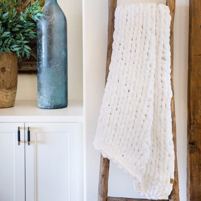 Little Infinite Love Blanket in White, chenille chunky knit, on wooden ladder in front of white cabinets