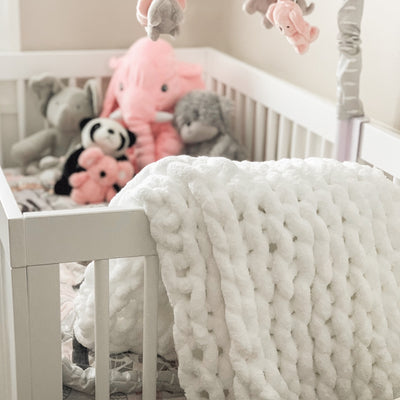 Little Infinite Love Blanket in White draped over baby's crib, used as nursery blanket, chunky knit