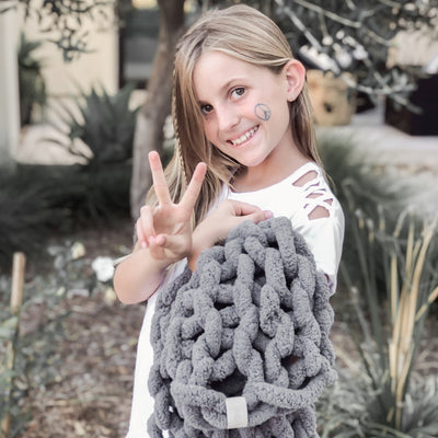 Young girl outside holding her Little Infinite Love Blanket in Slate, peace sign on her face Gia Poling BIG LOViE