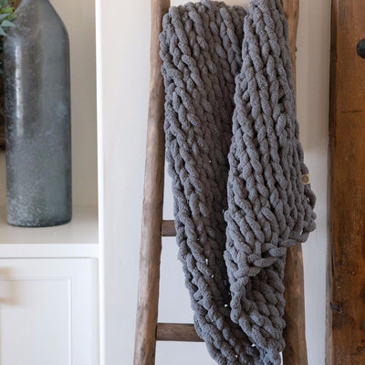 Little Infinite Love Blanket in Slate, chenille chunky knit, on wooden ladder in front of white cabinets