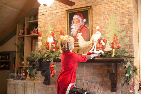 Kathy places another Santa and whimsical tree to complete the mantel.