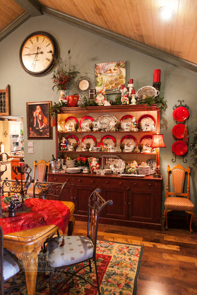 The brick red hutch is dressed with Christmas dishes and faux Christmas garlands and florals