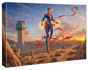 The morning sun dawns on a new day amplifying the glowing power emanating from Captain Marvel's hands as she watches over the desert base. - Gallery Wrap Canvas