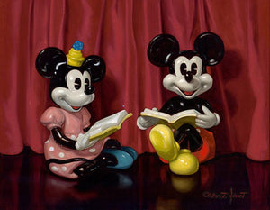 Minnie and Mickey reading their favorite book sitting in front of a red curtain.