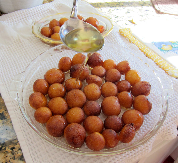 Pour sugar syrup over fried gulab jamun balls