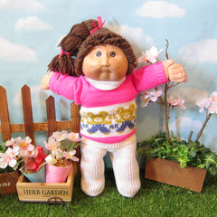 Cabbage Patch Kids girl doll with dark brown hair, brown eyes, dimples
