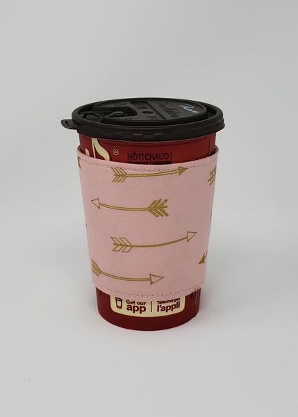 Reusable cup cozy displayed on a medium coffee cup - Gold Arrows on Pink