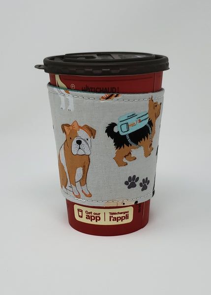 Reusable cup cozy displayed on a medium coffee cup - Teal Dogs Multi