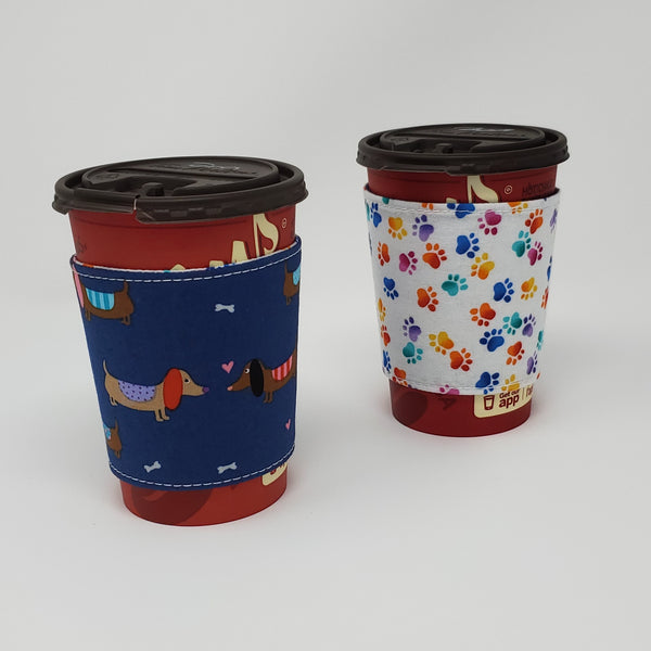 Reusable cup cozy displayed on a medium coffee cup - Blue Dachshunds and Hearts