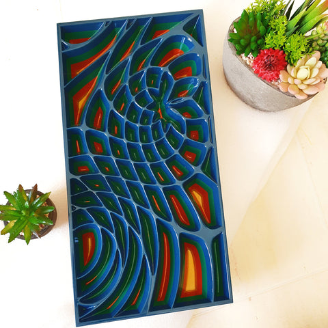 Wood wall art panel with blue and green colours made with wood. The geometric design in carved deeply into the wood creating a modern artwork.