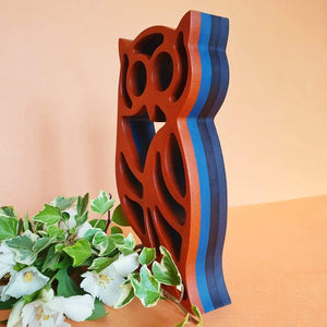 Wood carved owl creating a modern sculpture double faced. Being each side with different colours.