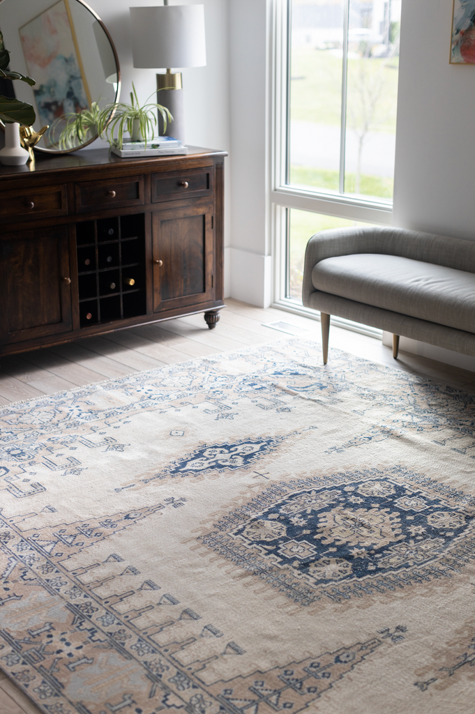 A cream and blue vintage rug styled in a bedroom.