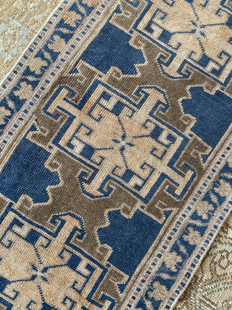 A tiny Turkish rug in a blue and brown colorway.