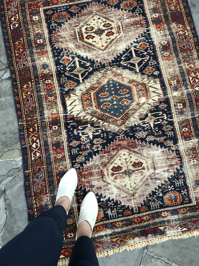 White shoes on an antique rug.