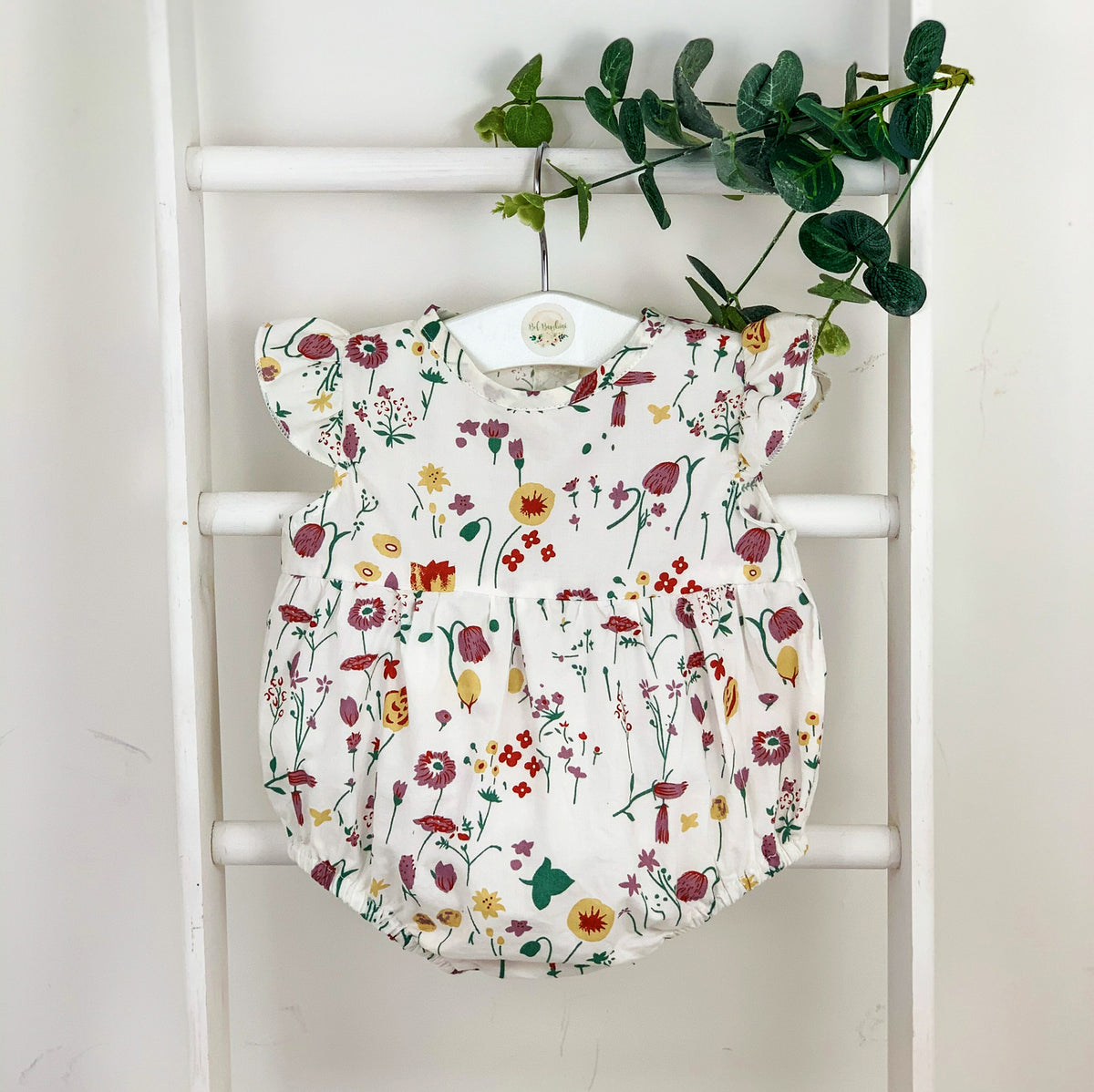 Baby girls autumn style. Our enchanted garden romper is available from 0-24m. The sweetest flutter shoulders and a beautiful floral print. Baby and toddler fashion. All season rompers at Bel Bambini baby boutique.