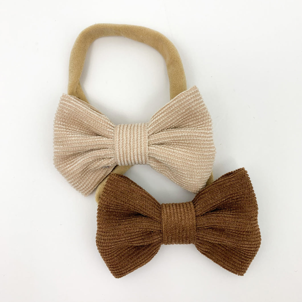 A duo pack of corduroy bow headbands for little girls. Perfect for babies and toddlers, available in a variety of colours. This pack has a latte and a chocolate shade in. Perfect to finish off your Bel Bambini outfits.