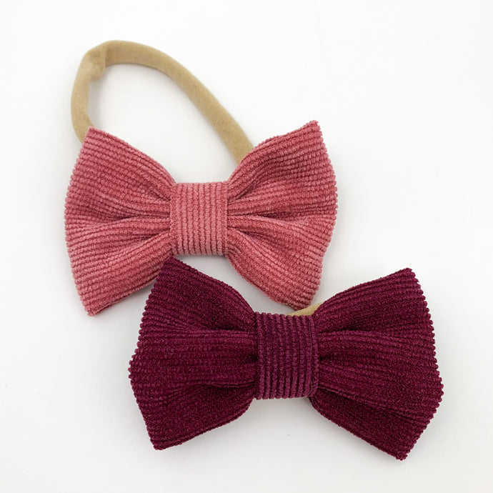 Baby girls bow headbands with a soft and stretchy band. Available in packs of two and a variety of colours. Red and berry headbands for toddler girls and babies. Exclusive to Bel Bambini baby boutique.