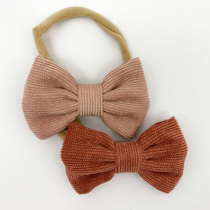 Corduroy bow headbands for baby girls, available in a variety of colours. This pack has peach and rust colours in, with a super soft and stretchy headband. Perfect to style your little ones Bel Bambini outfits with whilst looking adorably cute too. Exclusive girls headbands  at Bel Bambini baby boutique.