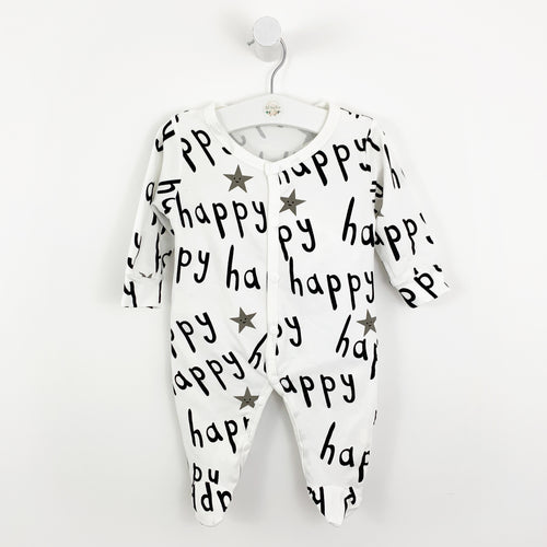 Babygrow, sleepsuit for baby boys and baby girls. Soft and comfortable, this cotton babygrow is white with the text 'happy' printed in black all over the sleepsuit.