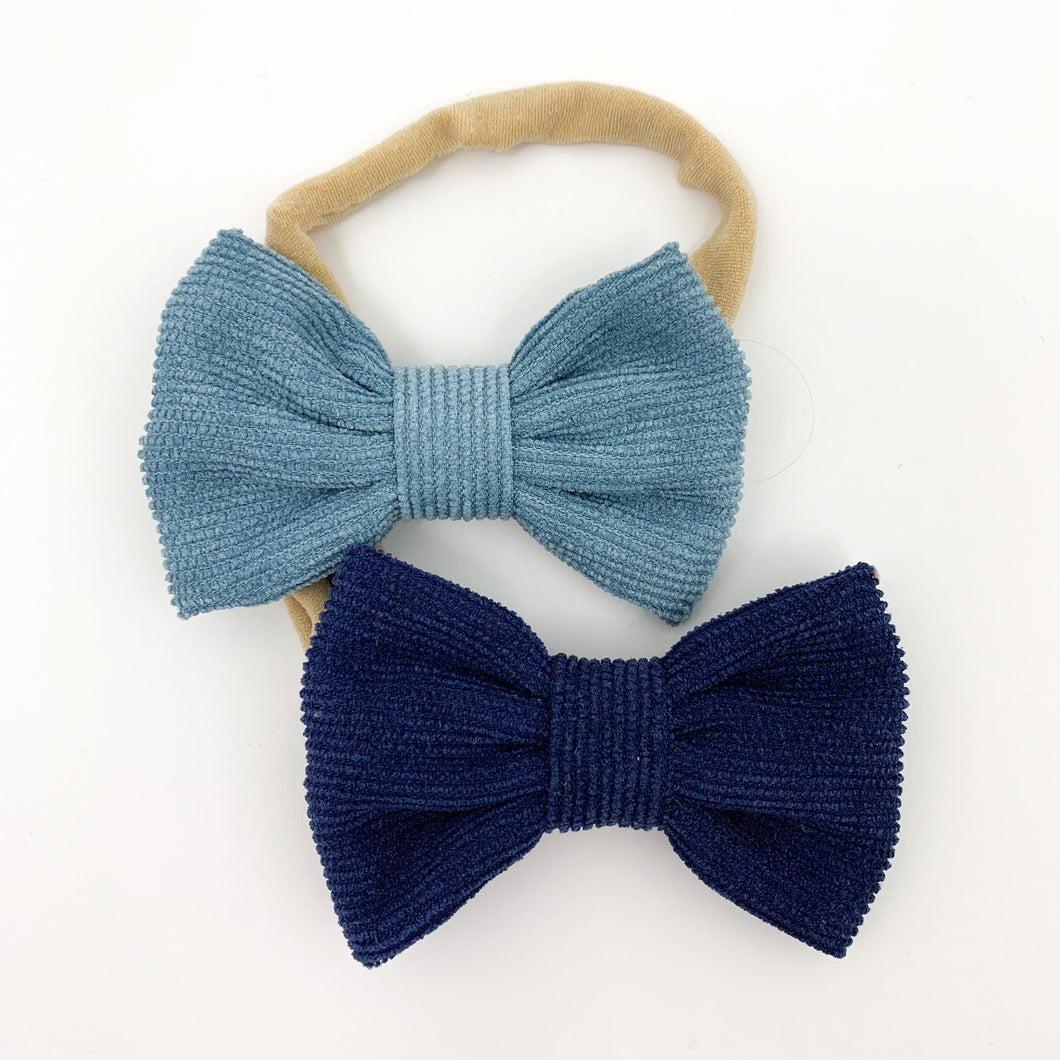 Two pack of headbands for girls. Super soft and stretchy band and a pretty corduroy bow. Blue and midnight coloured headbands for baby girls and toddler girls. Girls bow headbands available in a variety of colours exclusive to Bel Bambini baby boutique.