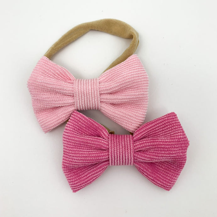 Pink headbands for little girls. A set of two bow headbands in candy pink and fuchsia pink. Corduroy bow with an elasticated headband. Soft and comfortable for you little girls head. Exclusive to Bel Bambini baby boutique.