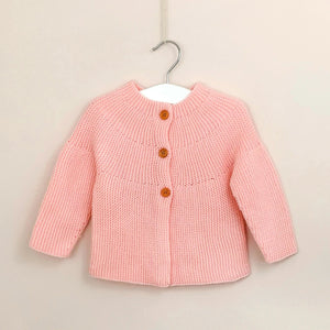 Girls Spanish style knitted cardigan in baby pink, fastened with three wooden buttons.