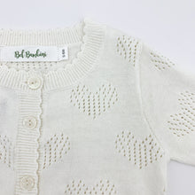 Load image into Gallery viewer, Scallop edging and heart detailing make this baby girls knitted cardigan such a sweet piece to finish off any outfit. Made from cottn yar, soft and comfortable for girls ages 0-24 months. Shop our baby and toddler clothing at Bel Bambini baby boutique.