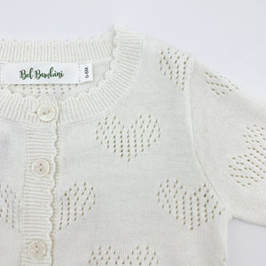 Scallop edging and heart detailing make this baby girls knitted cardigan such a sweet piece to finish off any outfit. Made from cottn yar, soft and comfortable for girls ages 0-24 months. Shop our baby and toddler clothing at Bel Bambini baby boutique.