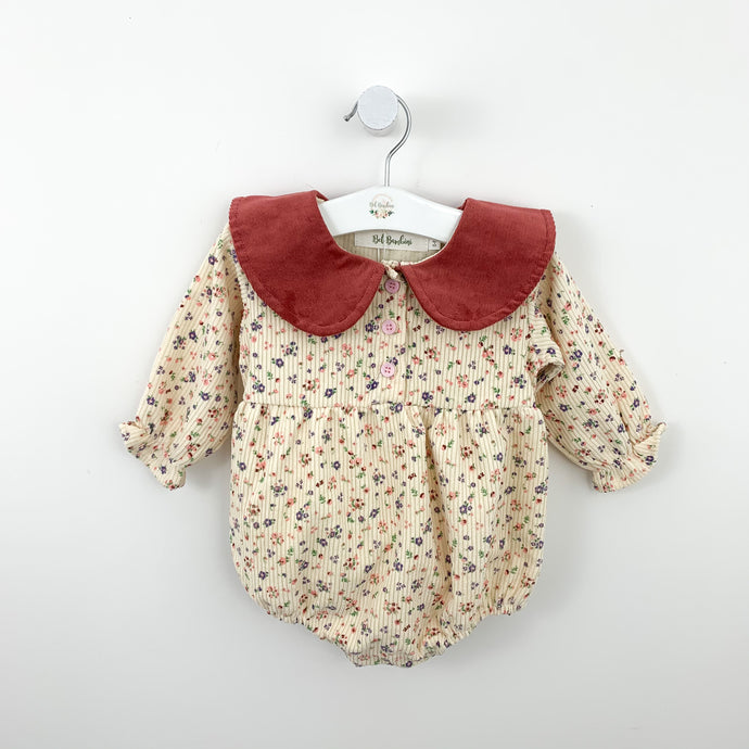 Girls romper suit in a ditsy floral print wiuth a peter pan statemnet style collar. Available for girls aged 0-24 months. Exclusive in Bel Bambini baby girls collection for spring.