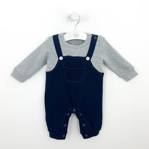 Boys all in one dungaree romper. Popper fastenings to the crotch for easy nappy changes. Long sleeve contrast grey tee and denim style dungarees that make this cute little omne piece look like two seperate pieces. Pocket detail to the front and button fastenings to the straps. Two popper fastenings to the left shoulder.