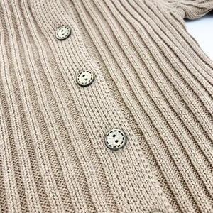 Detail shot of the 2x3 rib knitted romper for boys ages 0-24 months. Wood effect buttons down the front in a  warm neutral shade.