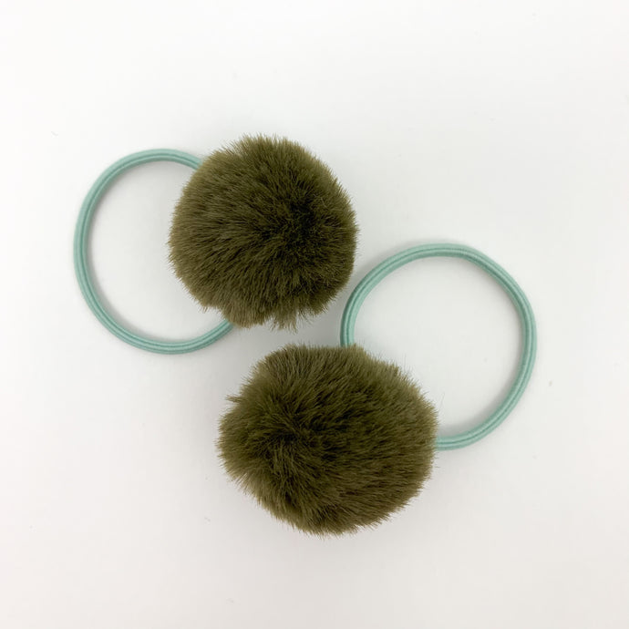 Olive green pompom bobbles for little girls. Fluffy pompoms on an elasticated band just make the sweetest little bobbles and perfect for pigtails and ponytails in toddlers hair. Accessories for little girls at Bel Bambini baby and toddler clothing boutique.