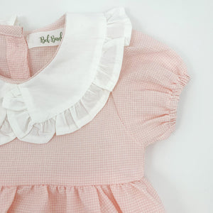 Detail shot of our girls pink romper showing the elasticated cuff on the sleeve hem and the pretty frill collar.