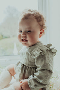 Baby girls romper exclusive to Bel Bambini. Stylish clothing for little girls. Gifts for baby and toddlers. Baby girl wearing our flutter detail romper in sage green.