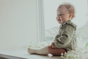Spring summer clothing for your baby and toddlers. Baby girl wearing our flutter detail romper in sage green.